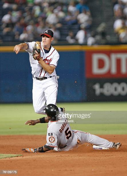 Kelly Johnson of the Atlanta Braves turns a double play while Ray Durham of the San Francisco Giants slides into second base during the game against...