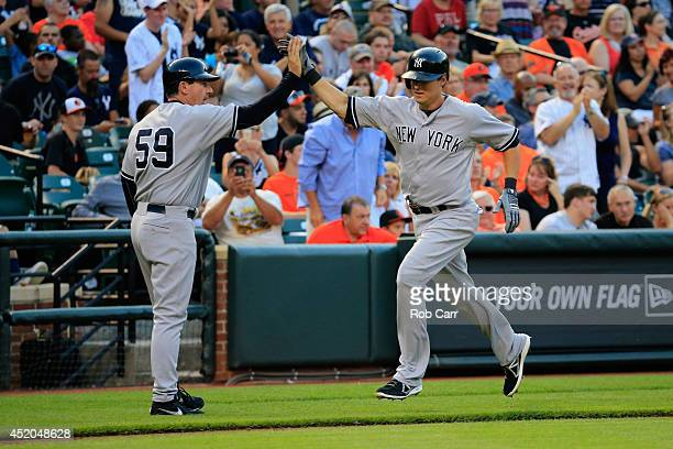 Kelly Johnson of the New York Yankees celebrates with third base coach Rob Thomson after hitting a solo home run against the Baltimore Orioles in the...
