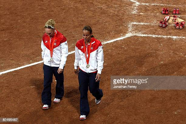 Kelly Kretschman and Tairia Flowers of the United States walk off the field after they left her spikes at home plate after USA lost 31 to Japan...