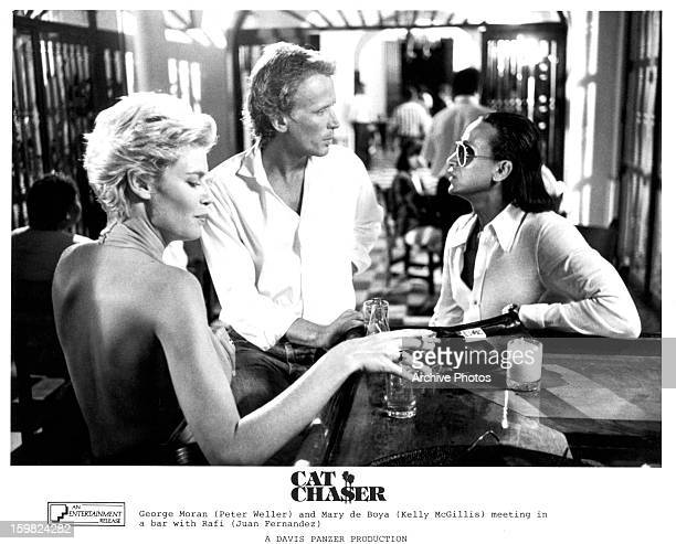 Kelly McGillis and Peter Weller meet with Juan Ferna‡ndez at a bar in a scene from the film 'Cat Chaser', 1989.