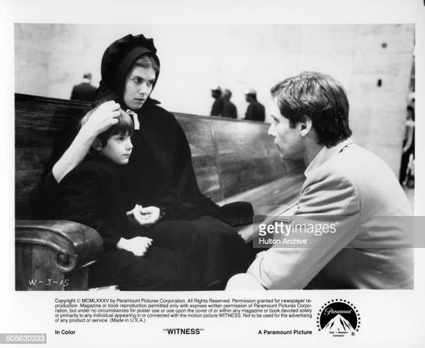 """Kelly McGillis holds Lukas Haas as Harrison Ford asks questions in a scene from the Paramount Pictures movie """"Witness"""" circa 1985."""