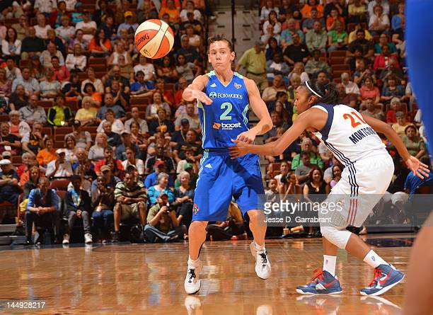 Kelly Miller of the New York Liberty passes the ball against Renee Montgomery of the Connecticut Sun during the game on May 20 2012 at the Mohegan...