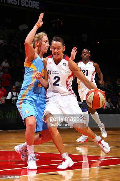Kelly Miller of the Washington Mystics drives against Catherine Kraayeveld of the Chicago Sky at the Verizon Center on August 20 2011 in Washington...