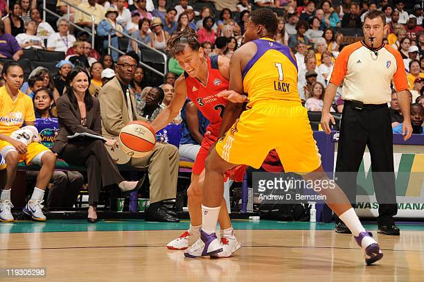 Kelly Miller of the Washington Mystics drives against Natasha Lacy of the Los Angeles Sparks during a game at Staples Center on July 17 2011 in Los...