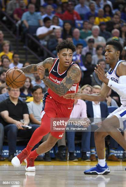 Kelly Oubre Jr #12 of the Washington Wizards drives on Patrick McCaw of the Golden State Warriors during their NBA basketball game at ORACLE Arena on...