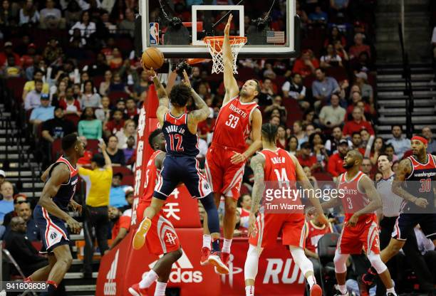 Kelly Oubre Jr #12 of the Washington Wizards goes up for a shot defended by Ryan Anderson of the Houston Rockets in the first half at Toyota Center...