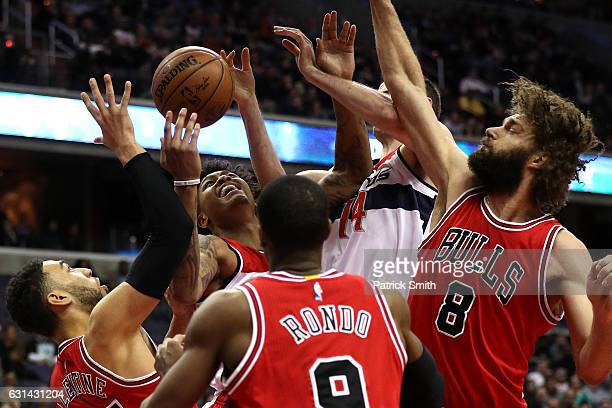 Kelly Oubre Jr #12 of the Washington Wizards pulls in a rebound in front of Denzel Valentine and Robin Lopez of the Chicago Bulls during the first...