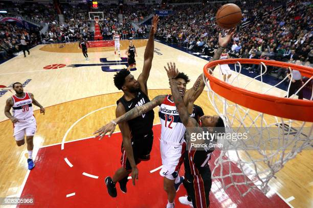 Kelly Oubre Jr #12 of the Washington Wizards shoots in front of Rodney McGruder of the Miami Heat during the first half at Capital One Arena on March...