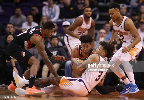 Kelly Oubre Jr #3 of the Phoenix Suns battles for a loose ball with Hassan Whiteside of the Portland Trail Blazers as Kent Bazemore and Elie Okobo...