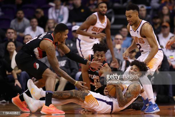 Kelly Oubre Jr #3 of the Phoenix Suns grabs a loose ball from Hassan Whiteside and Kent Bazemore of the Portland Trail Blazers during the second half...
