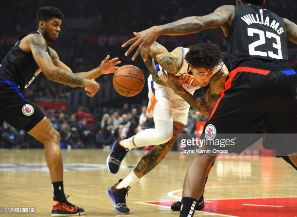 Kelly Oubre Jr #3 of the Phoenix Suns looses control of the ball as he is defended by Lou Williams and Tyrone Wallace of the Los Angeles Clippers...