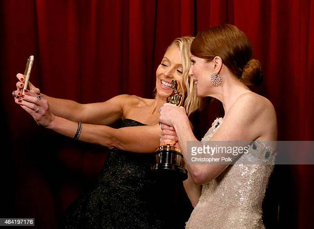 Kelly Ripa and award winner Julianne Moore take a selfie as Julianne holds her Oscar Statuette backstage during the 87th Annual Academy Awards at...