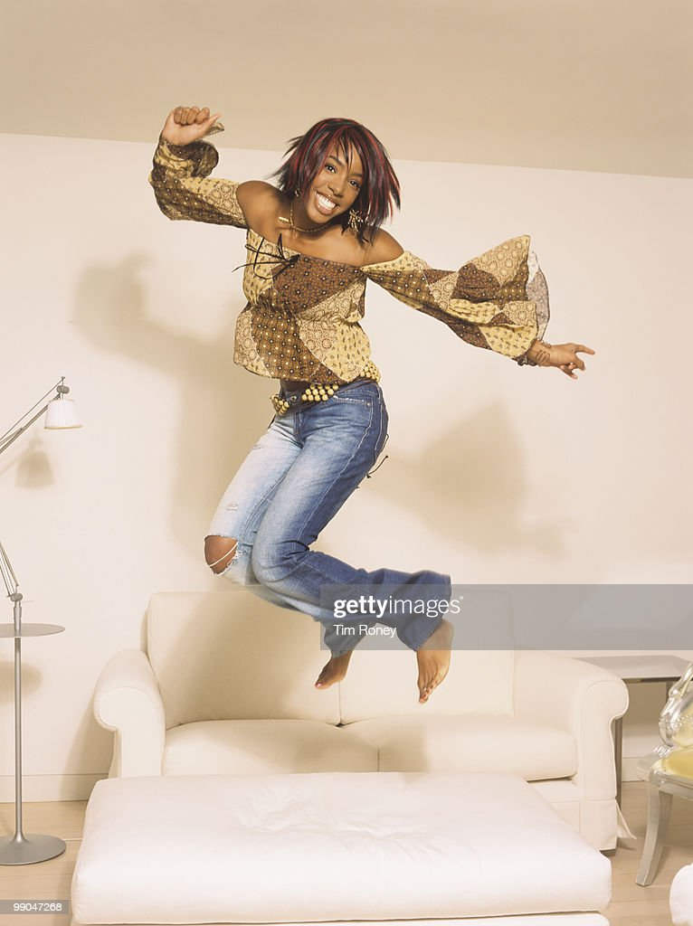 Kelly Rowland, singer and former member of 'Destiny's Child', jumping and smiling, circa 2002.