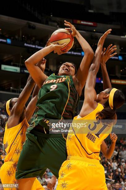 Kelly Santos of the Seattle Storm goes up for two points as Jessica Moore and Delisha Milton-Jones of the Los Angeles Sparks block the shot on...