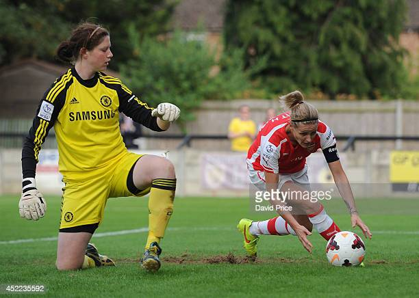 Kelly Smith grabs the ball after scoring a goal for Arsenal from the penalty spot as Marie Hourihan of Chelsea looks on during the WSL match between...