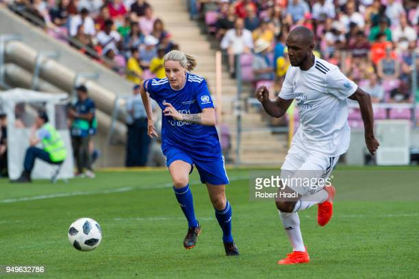 Kelly Smith vies with Eric Abidal during the UEFA Match for Solidarity at Stade de Geneva on April 21 2018 in Geneva Switzerland