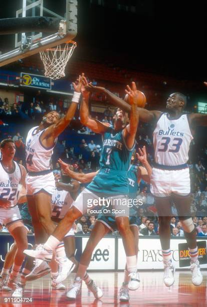 Kelly Tripucka of the Charlotte Hornets battles for a rebound with Jeff Malone and Larry Stewart of the Washington Bullets during an NBA basketball...