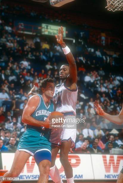 Kelly Tripucka of the Charlotte Hornets drives on Harvey Grant of the Washington Bullets during an NBA basketball game circa 1991 at the Capital...