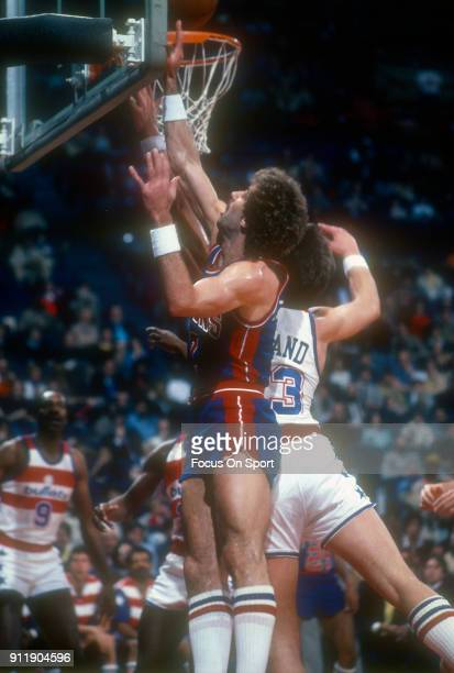 Kelly Tripucka of the Detroit Pistons battles for a rebound with Jeff Ruland of the Washington Bullets during an NBA basketball game circa 1982 at...