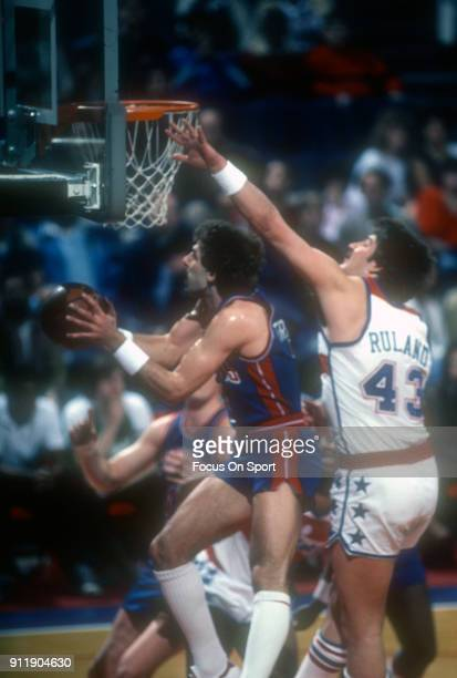 Kelly Tripucka of the Detroit Pistons goes in for a layup in front of Jeff Ruland of the Washington Bullets during an NBA basketball game circa 1983...