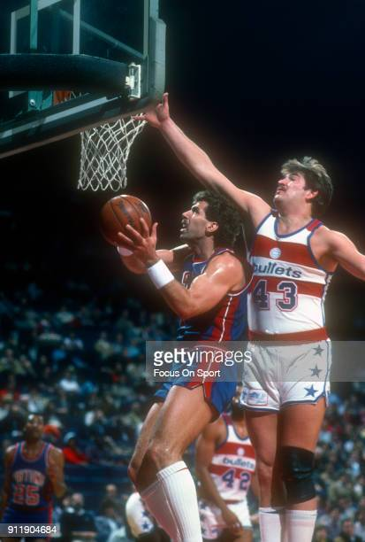 Kelly Tripucka of the Detroit Pistons goes in for a layup in front of Jeff Ruland of the Washington Bullets during an NBA basketball game circa 1984...