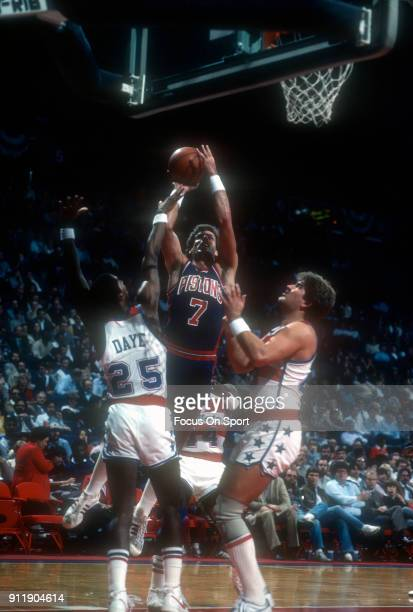 Kelly Tripucka of the Detroit Pistons goes to shoot over Darren Daye and Jeff Ruland of the Washington Bullets during an NBA basketball game circa...