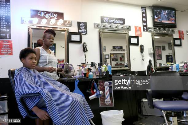 Kelly Tucker cuts the hair of Samuel Walls at the Prime Time barber shop which is located on Florissant Avenue where police and protesters repeatedly...