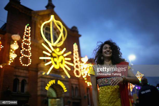 Kelly Vaduka laughs as friends photograph her in front of illuminations as she celebrates the Hindu festival of Diwali on October 23 2014 in...
