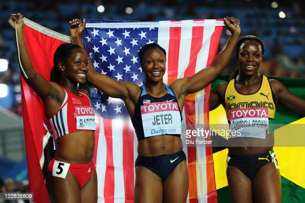 Kelly-Ann Baptiste of Trinidad and Tobago, Carmelita Jeter of United States and Veronica Campbell-Brown of Jamaica celebrate after the women's 100...