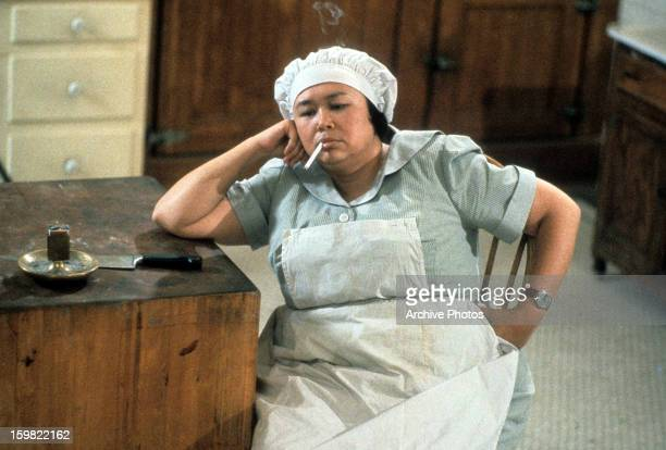 Kellye Nakahara dressed in a maids uniform while smoking a cigarette in a scene from the film 'Clue', 1985.