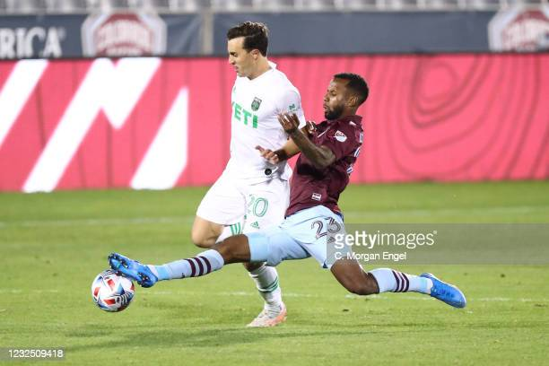 Kellyn Acosta of Colorado Rapids slide tackles Jared Stroud of Austin FC during the second half at Dick's Sporting Goods Park on April 24, 2021 in...