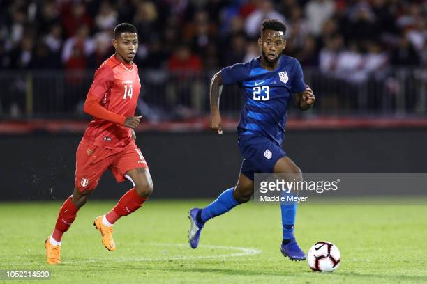 Kellyn Acosta of the United States dribbles past Andy Polo of Peru at Rentschler Field on October 16 2018 in East Hartford Connecticut