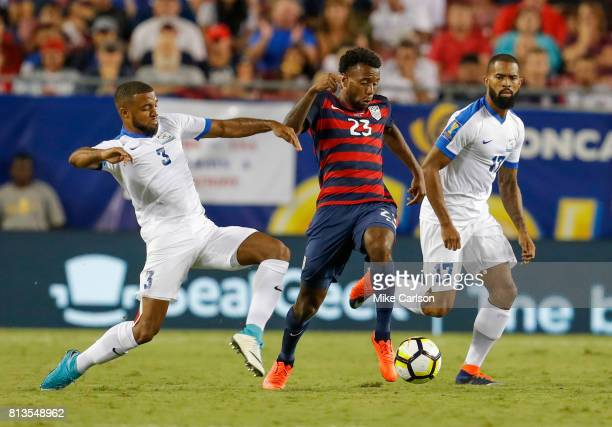 Kellyn Acosta of the United States splits the defense of Antoine JeanBaptiste and Kevin Parsemain Martinique during the first half of the CONCACAF...