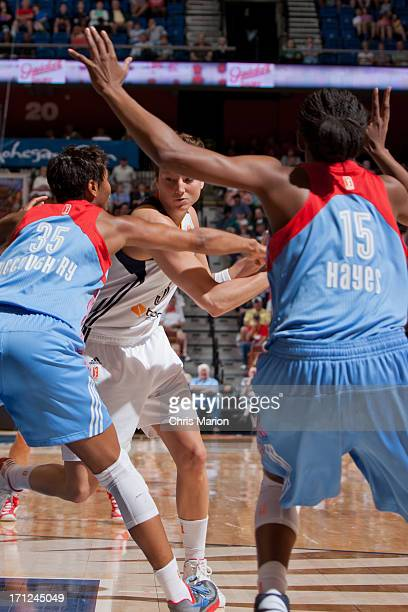 Kelsey Griffin of the Connecticut Sun looks to maneuver under pressure from Angel McCoughtry and Tiffany Hayes of the Atlanta Dream during a game at...