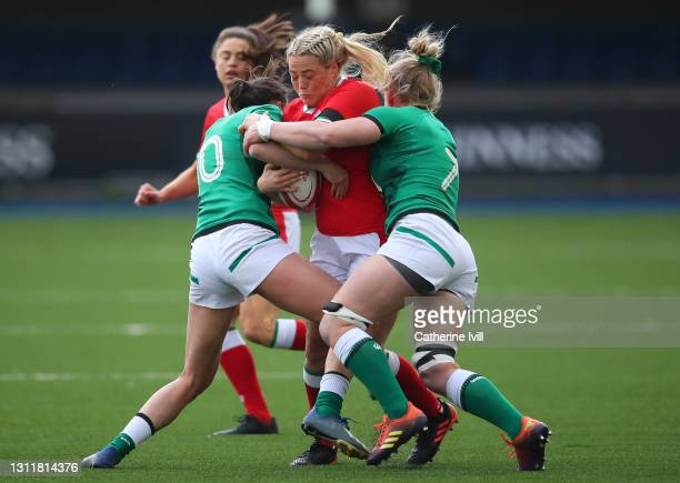 Kelsey Jones of Wales is tackled by Hannah Tyrrell and Claire Molloy of Ireland during the Women's Six Nations match between Wales and Ireland at...