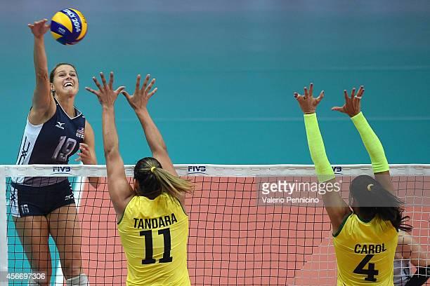 Kelsey Robinson of USA spikes as Ana Carolina Da Silva and Tandara Caixeta of Brazil block the FIVB Women's World Championship pool F match between...