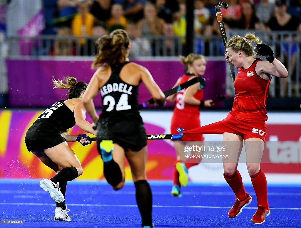 Kelsey Smith (L) of New Zealand vies for the ball with England's Hollie Pearne-Webb (R) during their women's field hockey semi-final match of the 2018 Gold Coast Commonwealth Games at the Gold Coast hockey centre on April 12, 2018. / AFP PHOTO / Manan VATSYAYANA