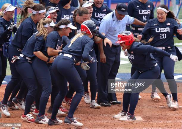 Kelsey Stewart of Team United States jumps on home plate as the umpire and her teammates watch her score the winning run after Stewart hit a walk-off...