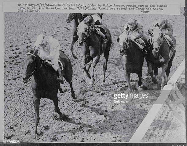 Kelso, ridden by Eddie Arcaro, pounds across the finish line to win the Brooklyn Handicap 7/22. Divine Comedy was second and Yorky was third.