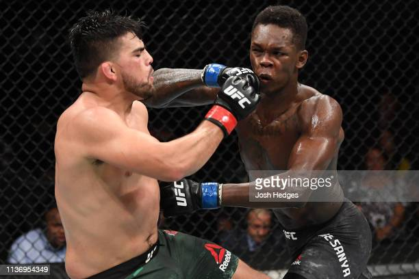 Kelvin Gastelum and Israel Adesanya exchange strikes in their interim middleweight championship bout during the UFC 236 event at State Farm Arena on...