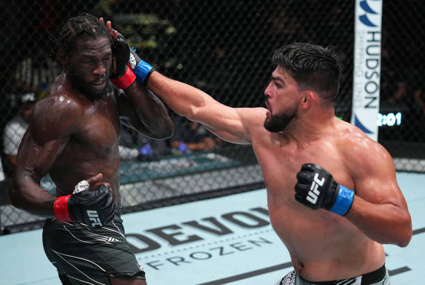 Kelvin Gastelum punches Jared Cannonier in a middleweight fight during the UFC Fight Night event at UFC APEX on August 21, 2021 in Las Vegas, Nevada.