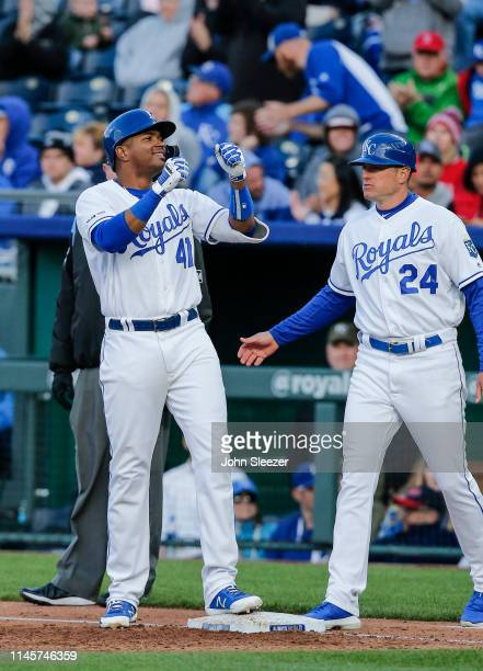 Kelvin Gutierrez of the Kansas City Royals celebrates his first major league hit with first base coach Mitch Maier for a two run single in the third...