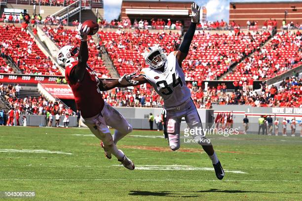 Kelvin Harmon of the North Carolina State Wolfpack misses a pass while defended by Bryce Hall of the Virginia Cavaliers at CarterFinley Stadium on...