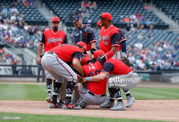 Kelvin Herrera of the Washington Nationals is helped by his teammates after an injury during the ninth inning against the New York Mets at Citi Field...