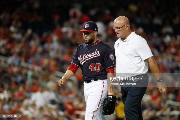 Kelvin Herrera of the Washington Nationals walks off the field with athletic trainer Paul Lessard after leaving the game with an apparent injury in...