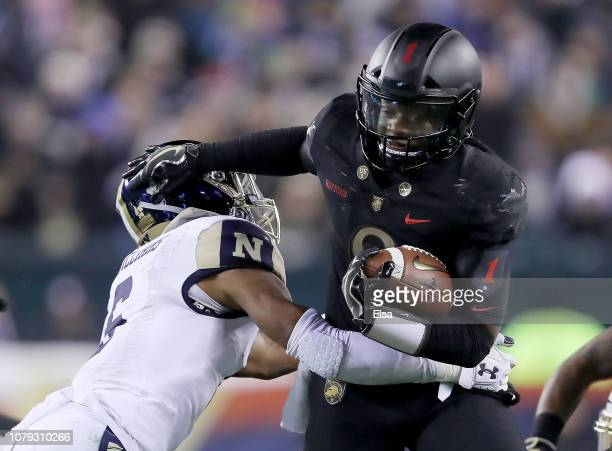 Kelvin Hopkins Jr #8 of the Army Black Knights carries the ball as Sean Williams of the Navy Midshipmen makes the tackle at Lincoln Financial Field...