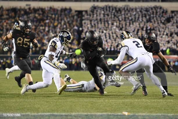Kelvin Hopkins Jr #8 of the Army Black Knights drives toward the end zone against Juan Hailey and Jarid Ryan of the Navy Midshipmen during the third...