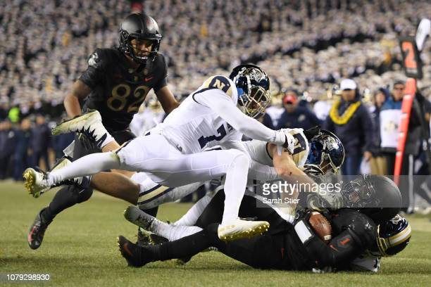 Kelvin Hopkins Jr #8 of the Army Black Knights is tackled by Khaylan Williams and Hudson Sullivan of the Navy Midshipmen during the third quarter of...