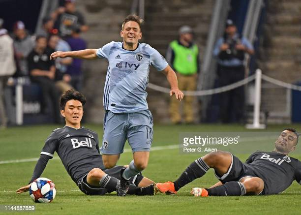 Kelyn Rowe of Sporting Kansas City gets taken down from behind by Hwang InBeom of Vancouver Whitecaps FC during the second half on May 18 2019 at...