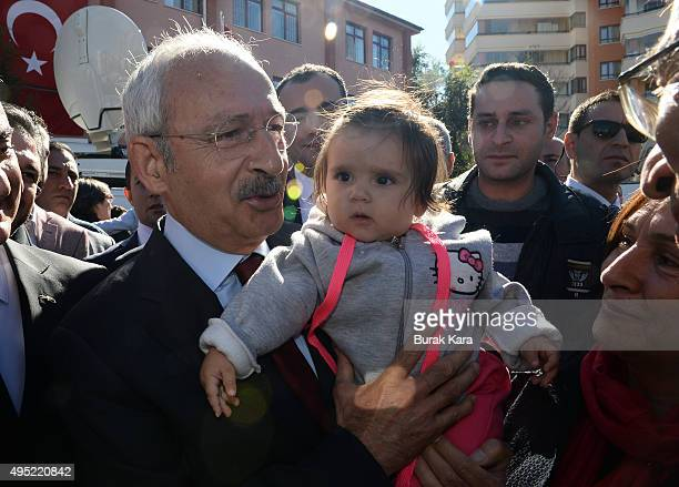 Kemal Kilicdaroglu leader of the main opposition Republican People's Party holds a child after casting his vote at a polling station during a general...